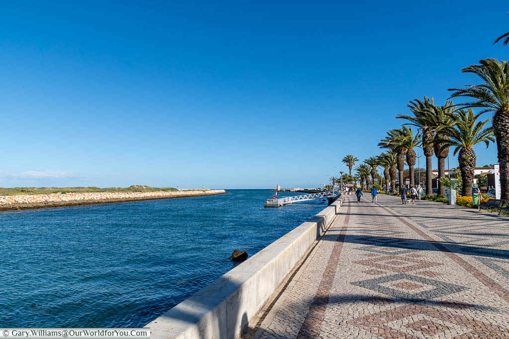 Next to the water the wide, tiled, palm-lined promenade in Lagos, Portugal