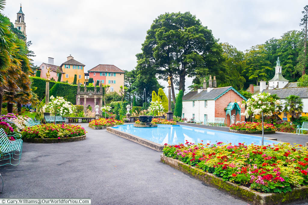 The central piazza of Portmeirion with its bright flower beds and central bond flanked on all sides with buildings in an Italian style