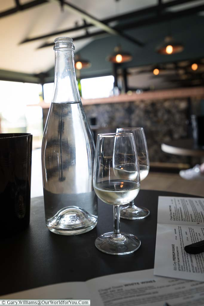 Two glasses of the light coloured Bacchus 2018 vintage in the tasting room accompanied with a bottle of water to refresh the palate.