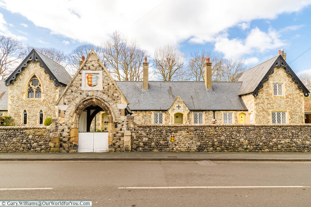 St Thomas' Hospital Almshouses rebuilt in a mid-19th-century gothic style, displaying the sign for the Cinque ports above the entrance arch, on the outskirts of Sandwich, Kent