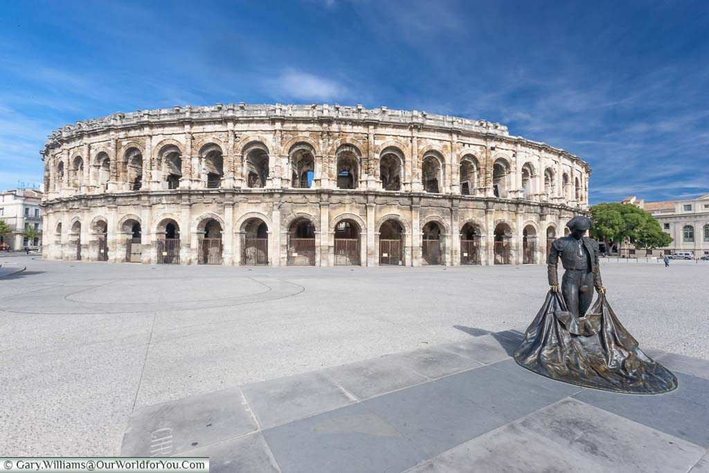 The brass statue of a bullfighter in front of the complete, two-storey, Roman arena in Nîmes.