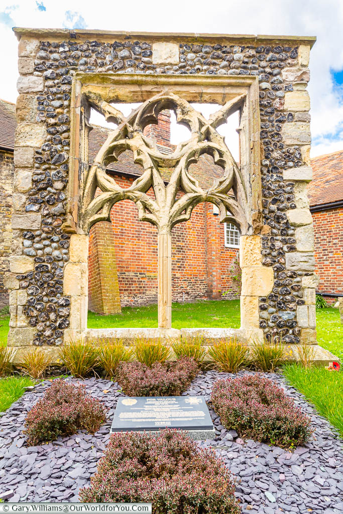The stone memorial to Victoria Cross recipient Augustus Charles Newman set in the ground in front a recovered gothic church window