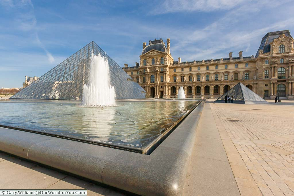 The outside of the Louvre from the corner of the pond with a fountain in front of the pyramid. It's a bright day in Paris, and suprisingly it's quiet in the Napoléon court in front of the museum.