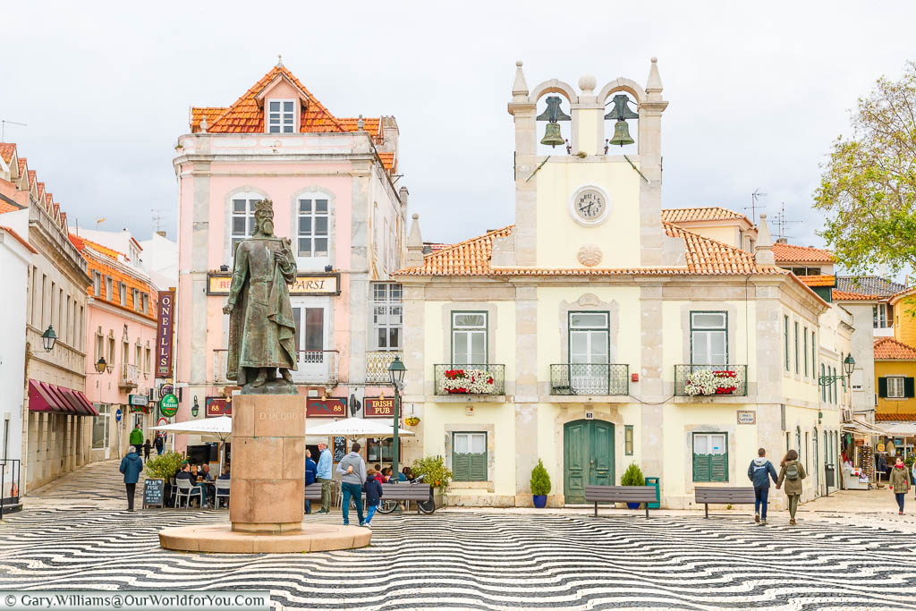 The Praca 5 de Outubro tiled in black and white with historic buildings lining this square in Cascais, Portugal