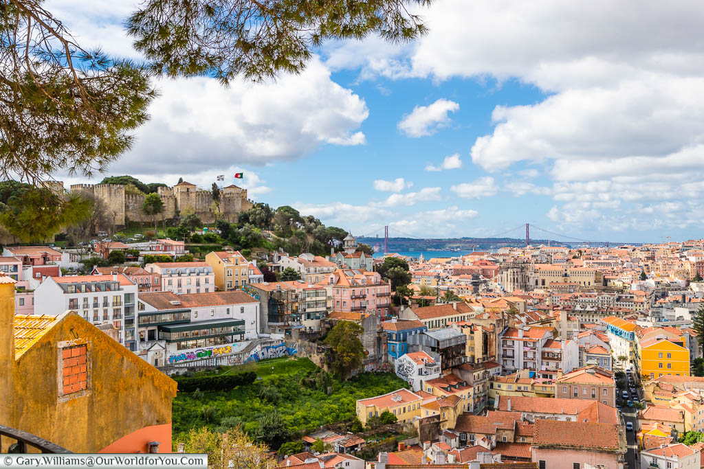 The view from Miradouro da graça over the rooftops of Lisbon, Portugal. In the near distance you can see the castle on the hillside, and in the distance the April 4th Bridge over the River Tagus