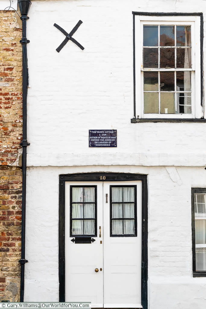 A 16th-century terraced town cottage in painted white, with black features, once home to a Thomas Paine, in Sandwich, Kent
