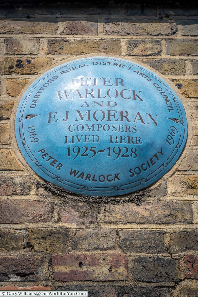 A commemorative blue plaque to the composers E.J. Moeran and Peter Warlock above a house on Eynsford High Street