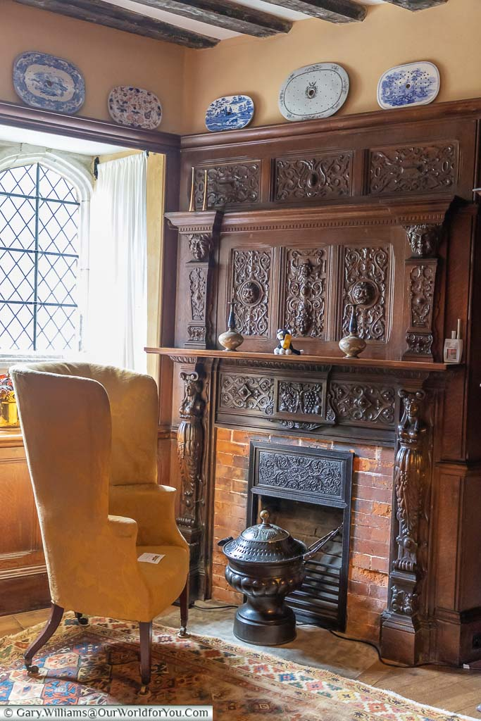 A high back chair in front of a fireplace, with an ornate dark wood surround, in the corner of the Billiard Room of Ightham Mote