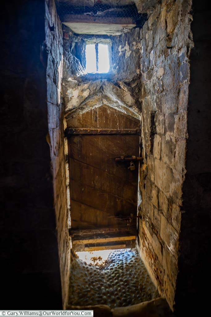 Light seeping into the interior of the basement of Deal Castle past an ancient wooden door.