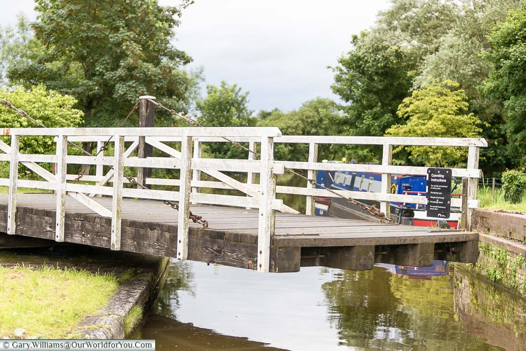 A part opened, pedestrian, swing bridge on the Kennet and Avon canal with a board detailing it's operating instructions for the safety of all waterway users.