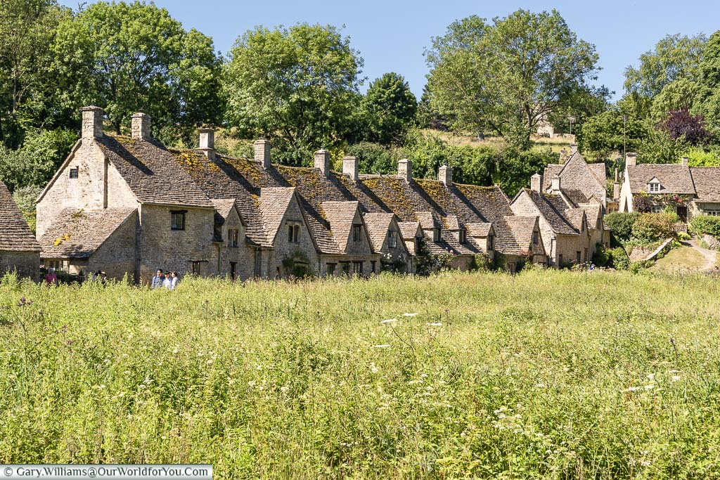 Looking across a field to the Cotswold stone terraced cottages of Arlington Row, Bibury
