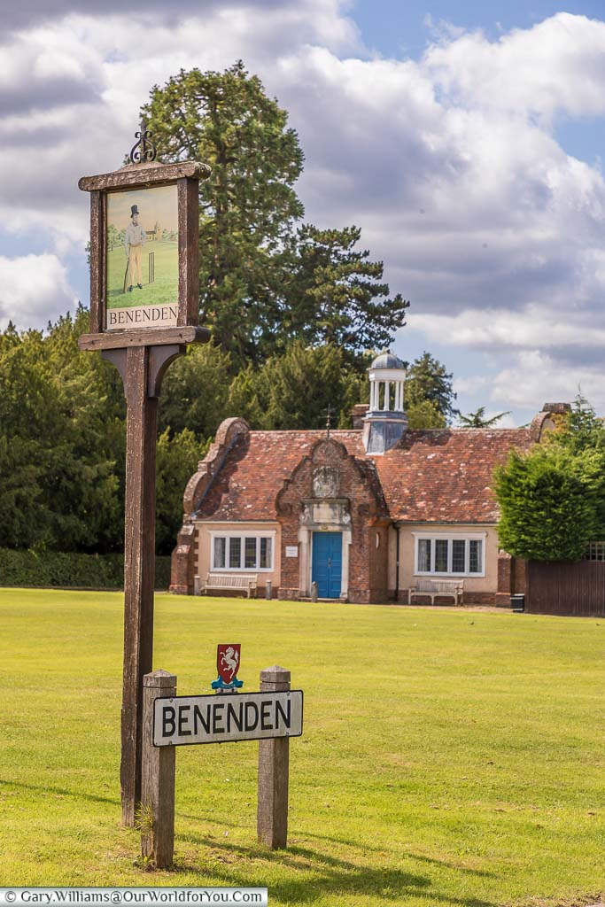The village sign for Beneden in Kent depicting a man playing cricket whilst wearing a top hat