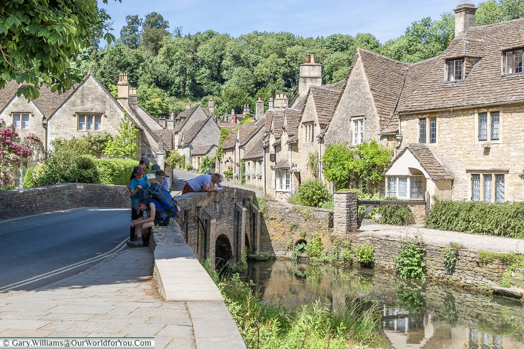 A family gathered on a small stone bridge over the By Brook in Castle Combe. The road leading over the bridge he is flanked on either side my beautiful stone buildings in the traditional Cotswold style of a golden sandy stone.