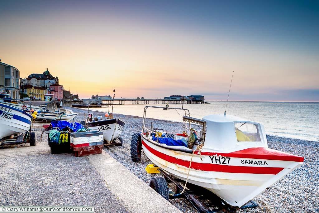 A small fishing boat on the shore at Cromer at dusk