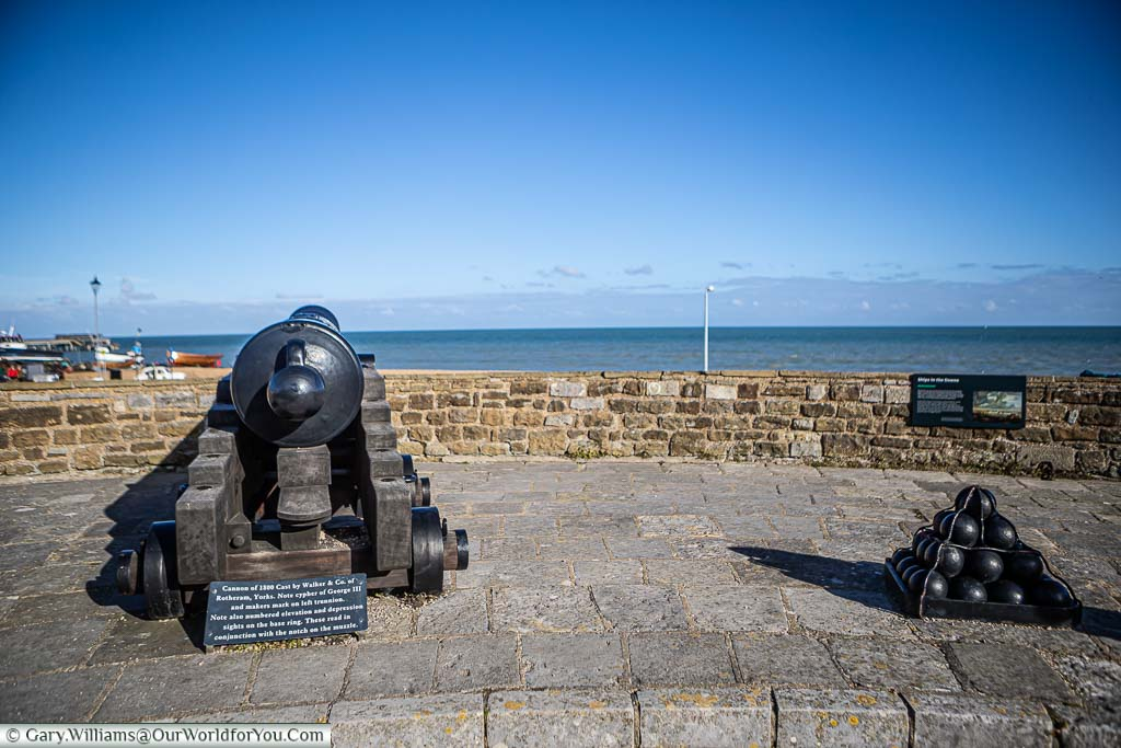 An 18th/19th century cast-iron cannon, and a stack of cannonballs placed on the walls of Deal Castle facing out to sea