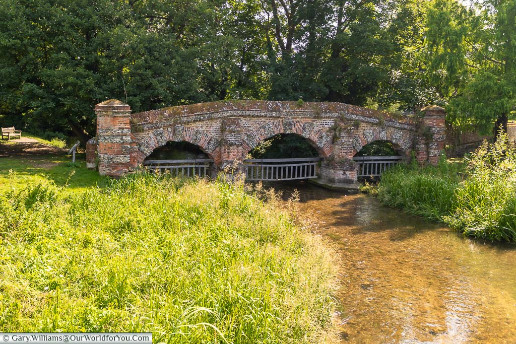 A brick-built, three arch structure, with wooden gated suspended from each arch over the River Darent in Farningham, Kent