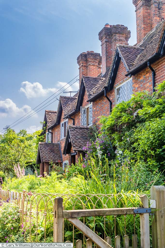 A row of red-brick terrace cottages, with beautiful old English styled country front gardens