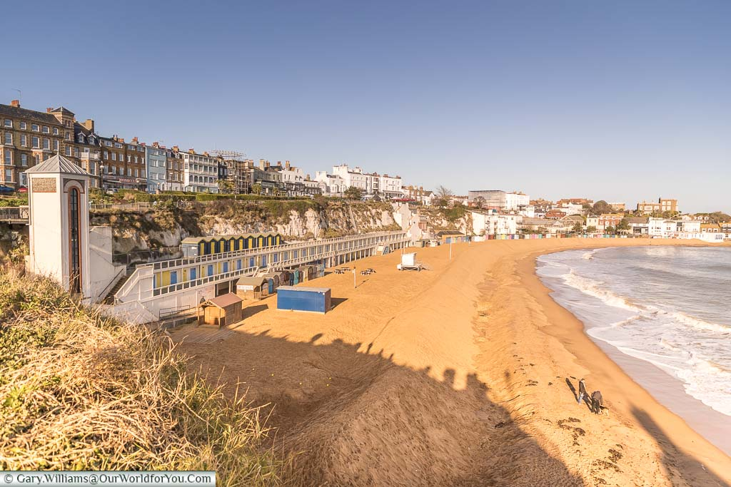 A view of Viking Bay as it sweeps around towards the harbour. On the left hand side you can see the lift What takes you to and from the promenade. also stretched out along the sea front you can see the bathing cabins.