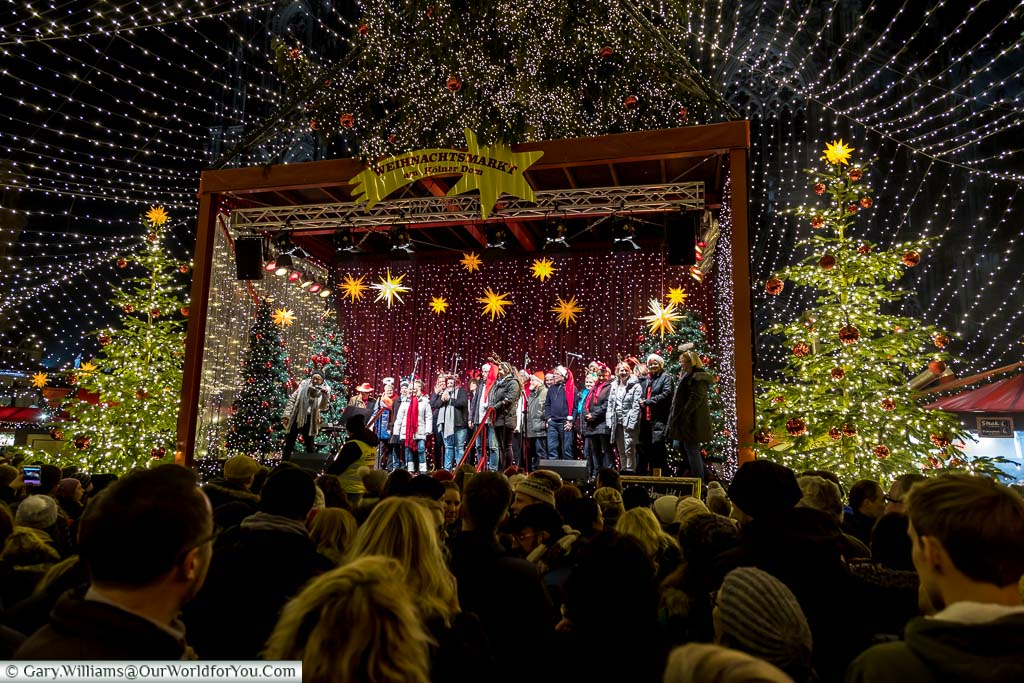 Crowds in front of a carol concert on stage in the Dom Christmas Market, under a blanket of fairy-lights