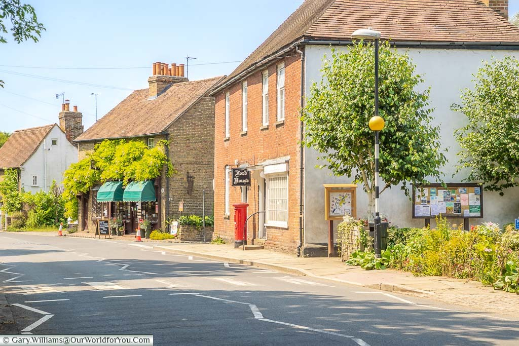 Eynsford High Street by the old bridge with a red letterbox in front of Ford House, and the old gift shop in the distance