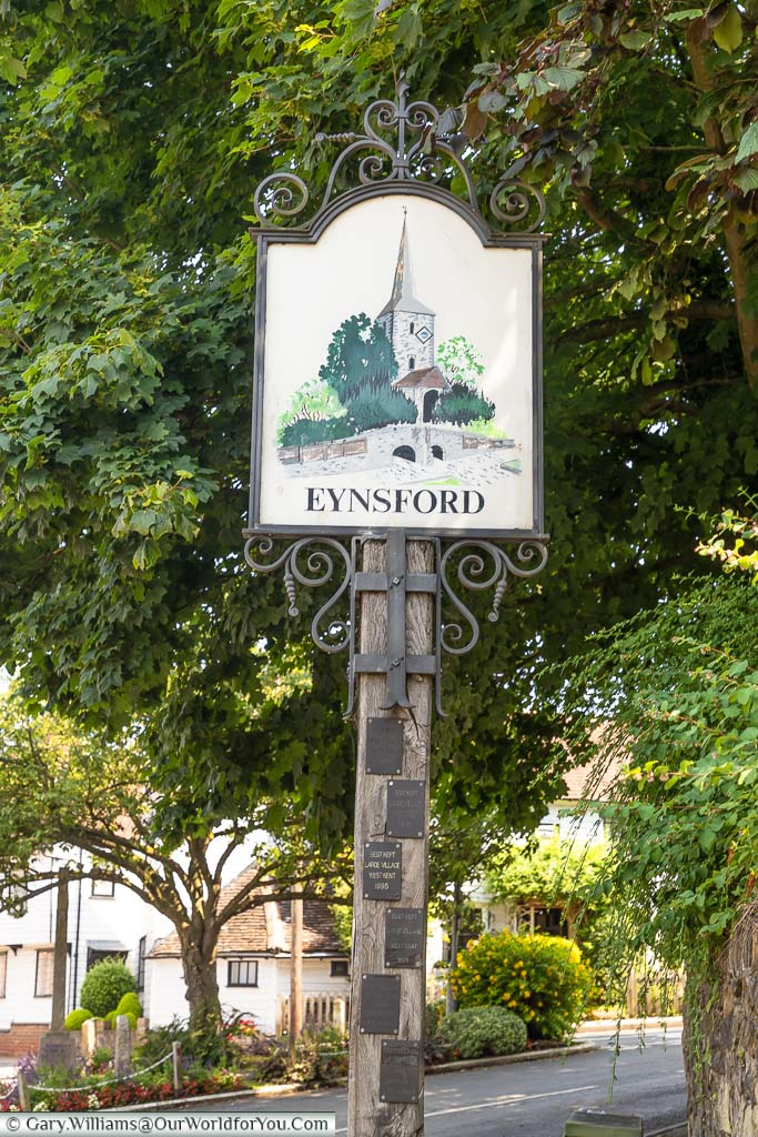 The village sign for Eynsford featuring the old stone bridge and St Martin's Church