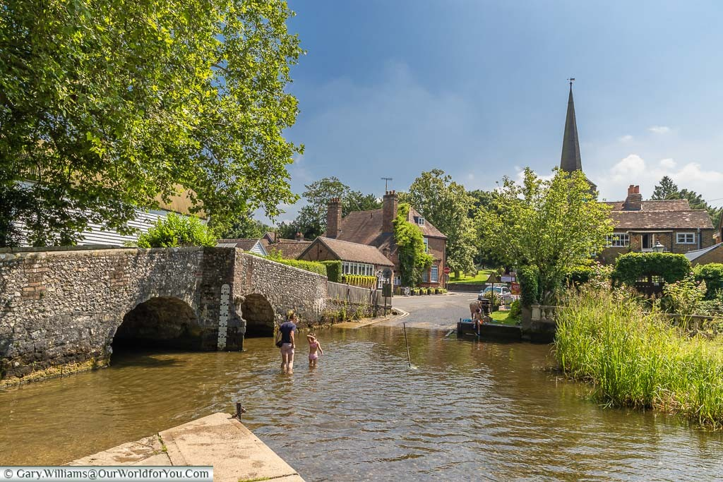 The view across Eynsford ford, with a mother and child paddling in the water with the spire of St Martin's Church in the background