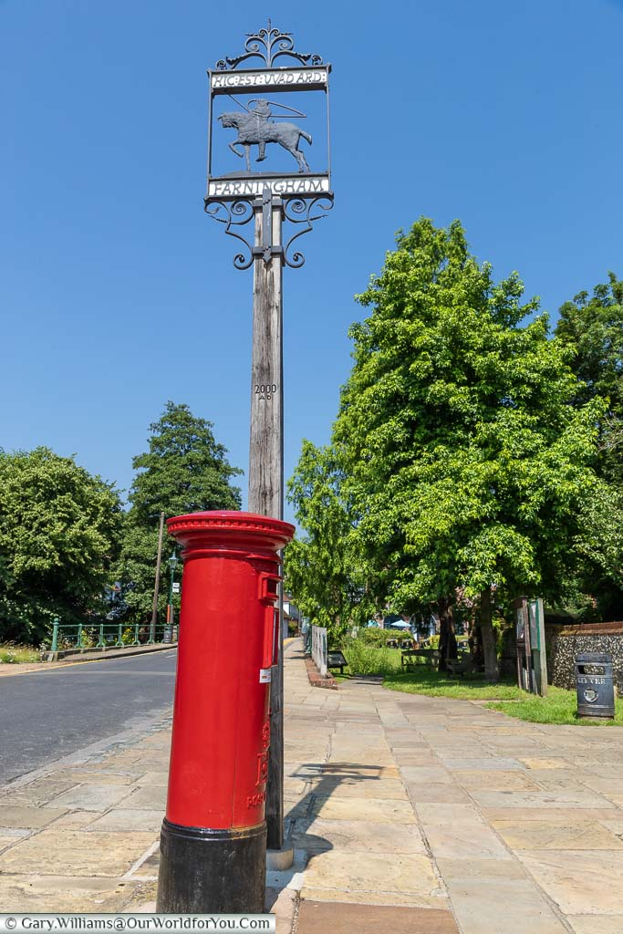 A bright red letterbox next to the Farningham village sign featuring the image of Hic Est Wadard copied from the Bayeux Tapestry.