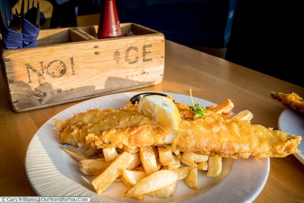 A plate of Fish 'n' Chips at No1, Cromer, with a generous portion of battered cod atop golden chips, garnished with a lemon and a sprig of parsley