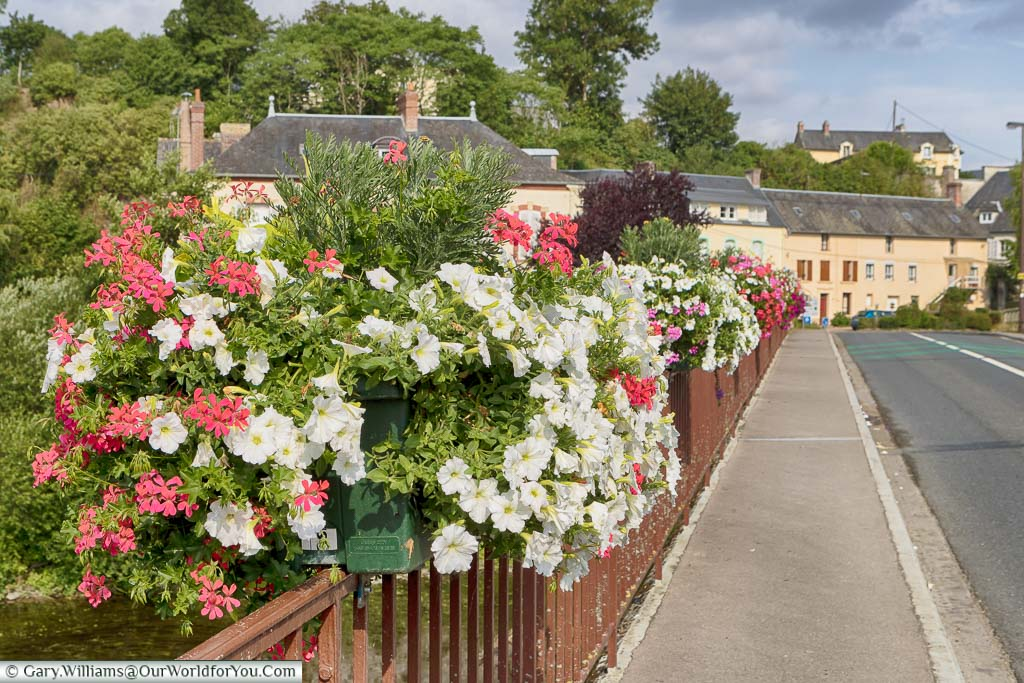 A bridge, lined with flowers in windowboxes, on the route 'La Suisse Normande' through Normandy.
