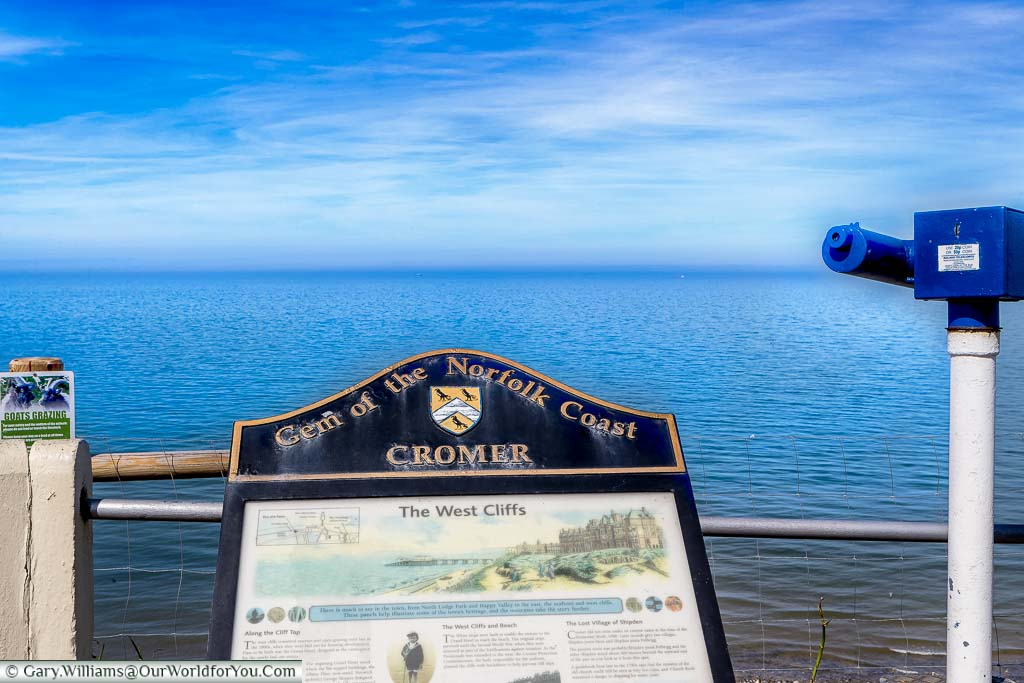 """A view of the shoreline in Norfolk behind an information board declaring Cromer as """"Gem of the Norfolk Coast""""."""