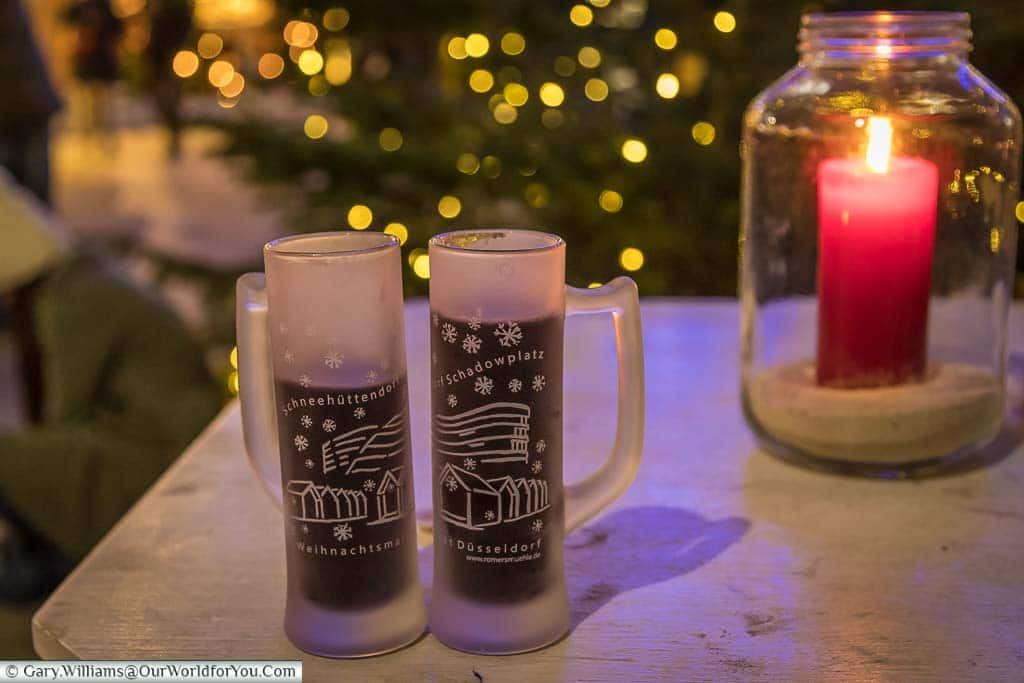 Two frosted glasses of Gluhwein, next to a candle lantern, on an outside table in the Schadowplatz market in Düsseldorf