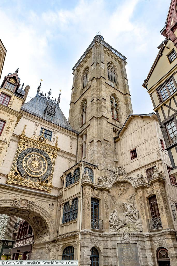 Rouens famous Gros-Horloge. An ornate, gold-trimmed, clock mounted above an arch in one of the old town's thoroughfares next to a stone belfry.