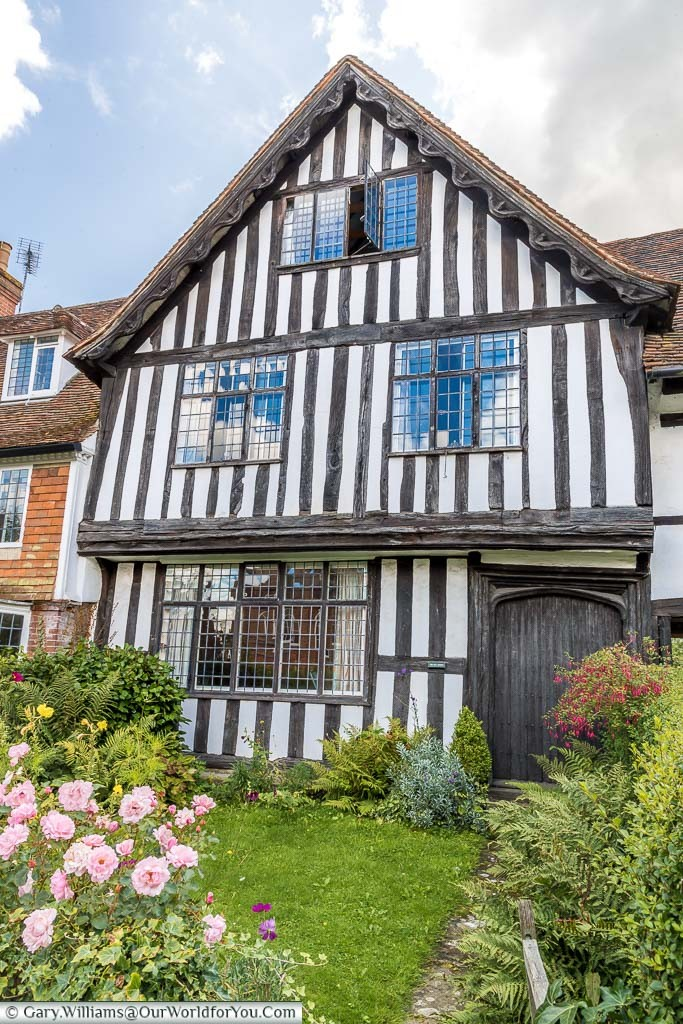 A black and white half-timbered Tudor period home with a cottage garden to the front. One of the older houses in Cranbrook