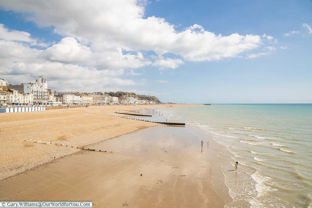 The view of Hastings beach and seafront from the pier on a bright sunny day