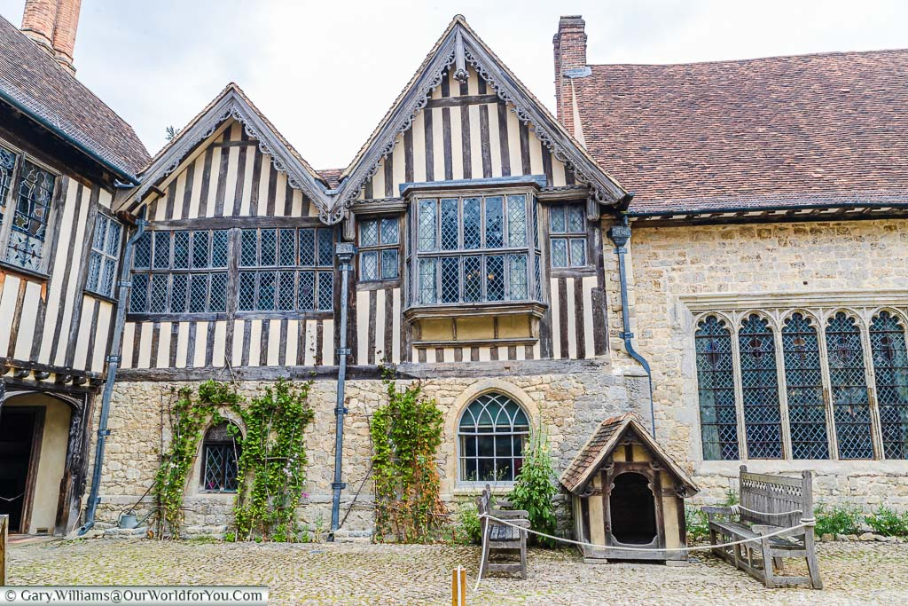 Inside the open Great Courtyard of Ightham Mote, lined with the medieval facades of the different elements of the manor house.