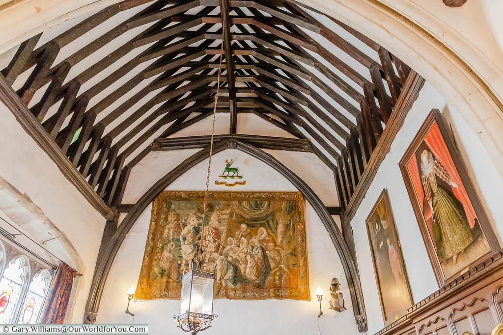 Portraits, a tapestry and a stained glass window line the Great Hall of Ightham Mote with its vaulted ceiling.