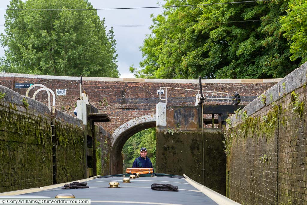 Our canal boat is entering a lock. One of the lock gates is open, while the other is closed, while the 'skipper' pilots the vessel into the narrow lock.
