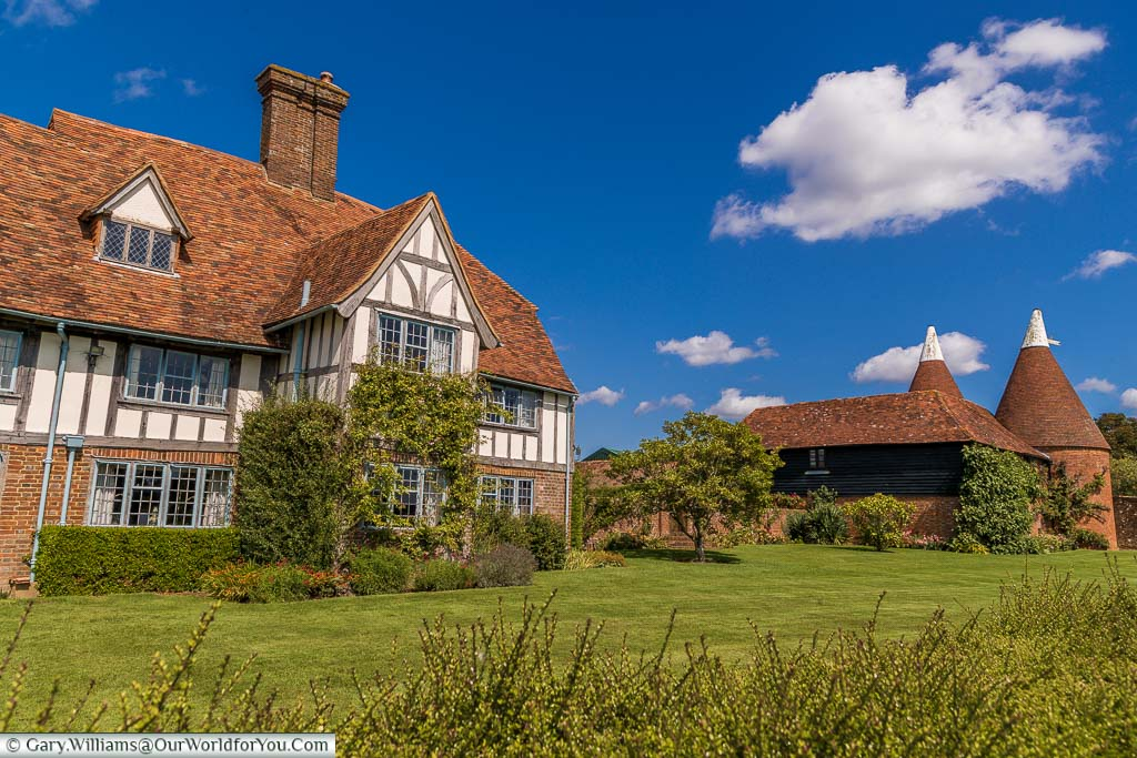 A pretty Tudor half-timbered house alongside two white topped oast houses in Rolvenden, Kent