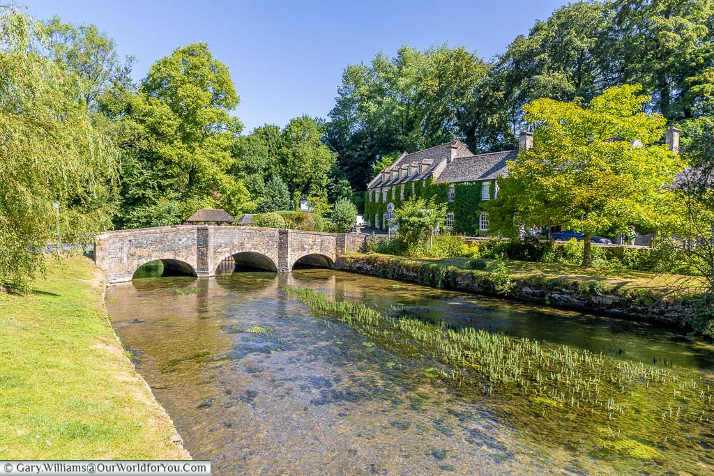 The River Coln flowing under a stone bridge in the beautiful Cotswold village of Bibury