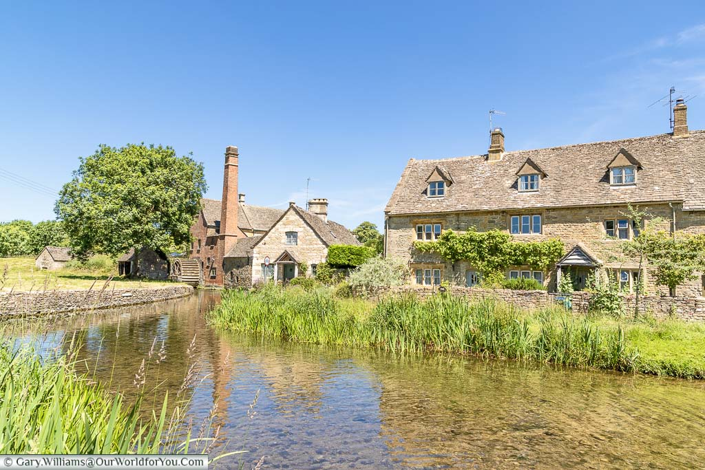 An idyllic Cotswold scene of a very shallow, slow flowing, river in front of a Cotswold home and a water mill with a tall brick built chimney In a village called Lower Slaughter