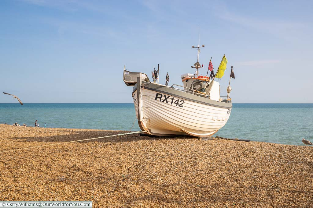 A small fishing trawler, with the identifier RX142, on the single beach at Hastings on the East Sussex coast