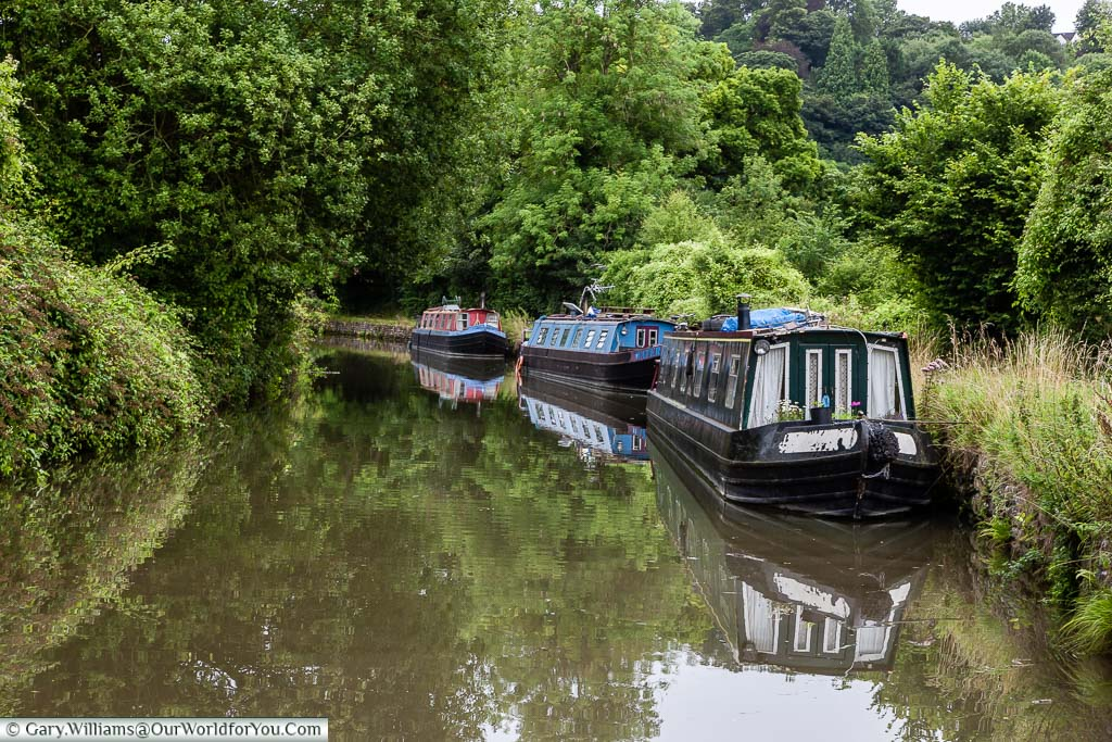Three narrow beam canal boat moored up as we pass slowly on our relaxing trip along the Kennet and Avon canal.