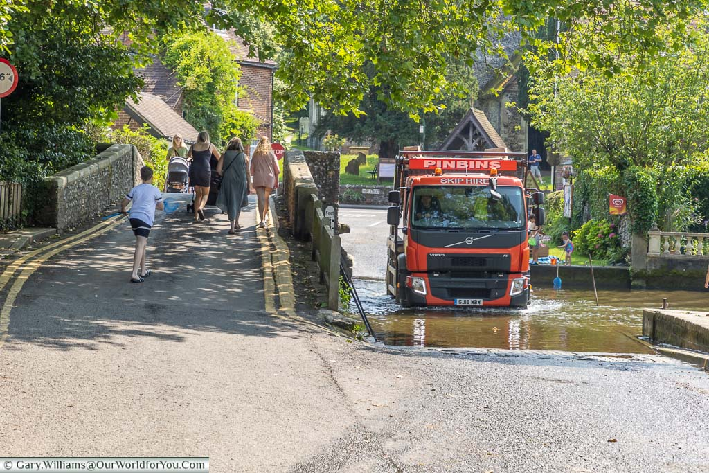 A lorry passing through Eynsford ford next to the old stone bridge