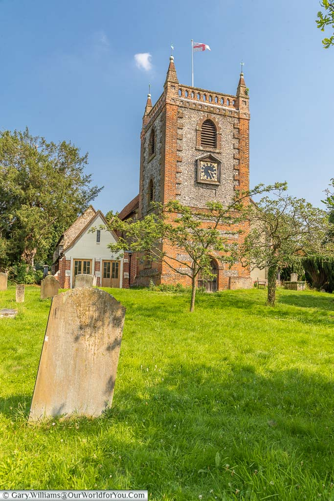 The tower of St Peter and St Paul Church in Shore, flying the cross of St George, as seen from the churchyard