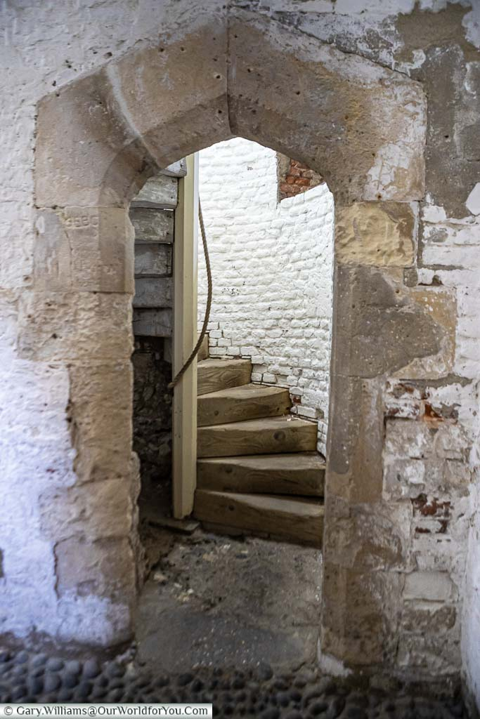 A heavy stone archway leading to a spiral staircase within Deal Castle