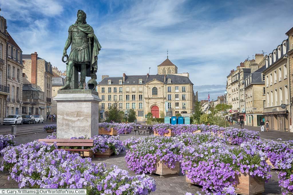 Boxed purple & mauve flowers surround the statue of Louis XIV in Place Saint-Sauveur in Caen, Normandy