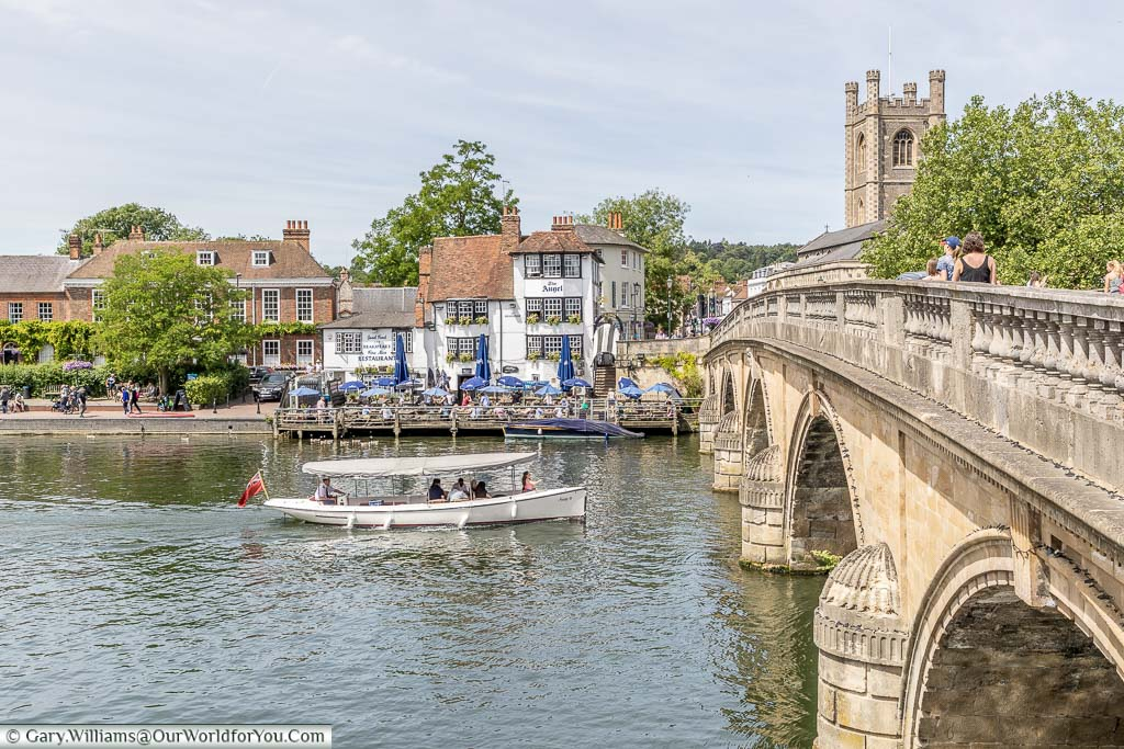A small pleasure boat heading under the Henley Bridge in front of the The Angel on the Bridge pub in Henley on Thames