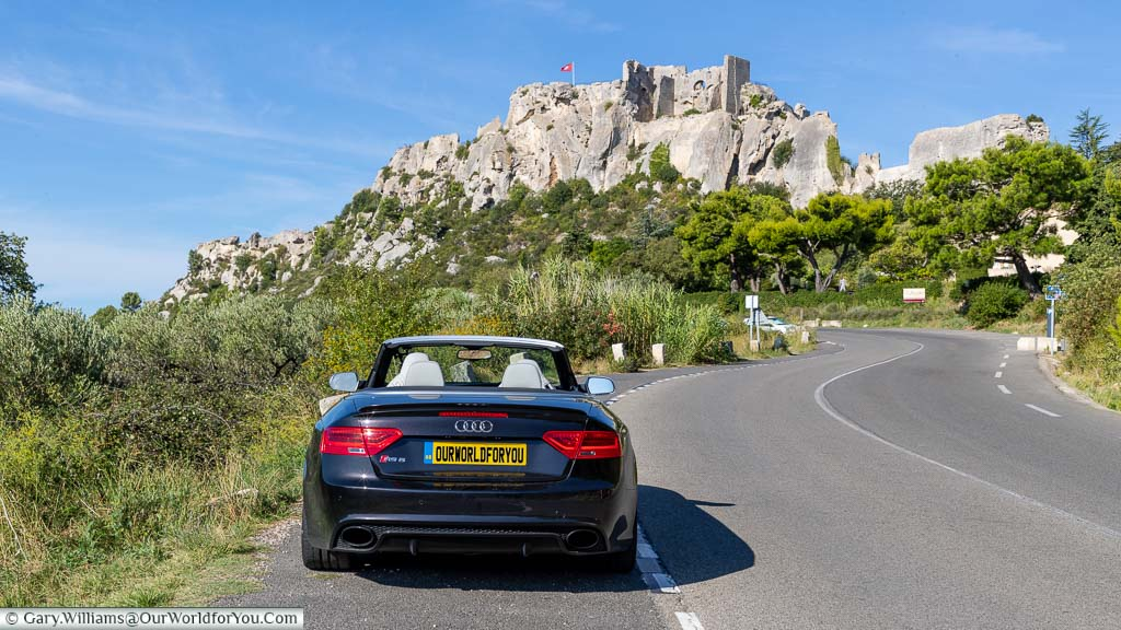 Our Audi convertible parked up on the roadside as it curves up towards to the hillside village of Les Baux-de-Provence. The remains of the ruins of Château des Baux sit high on the rock face.