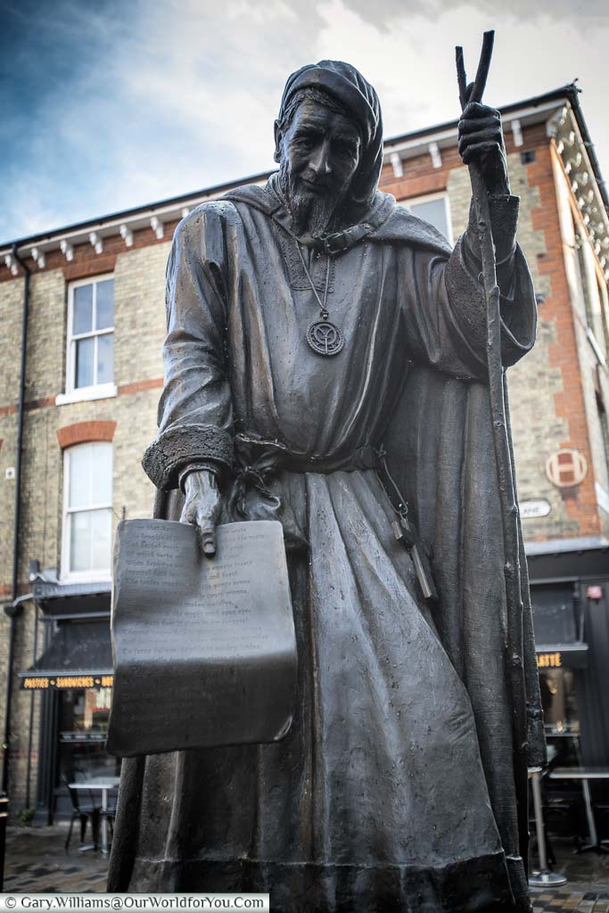 A statue to Geoffrey Chaucer, dressed as a pilgrim, sharing his Canterbury Tales, in the High Street of Canterbury, Kent.