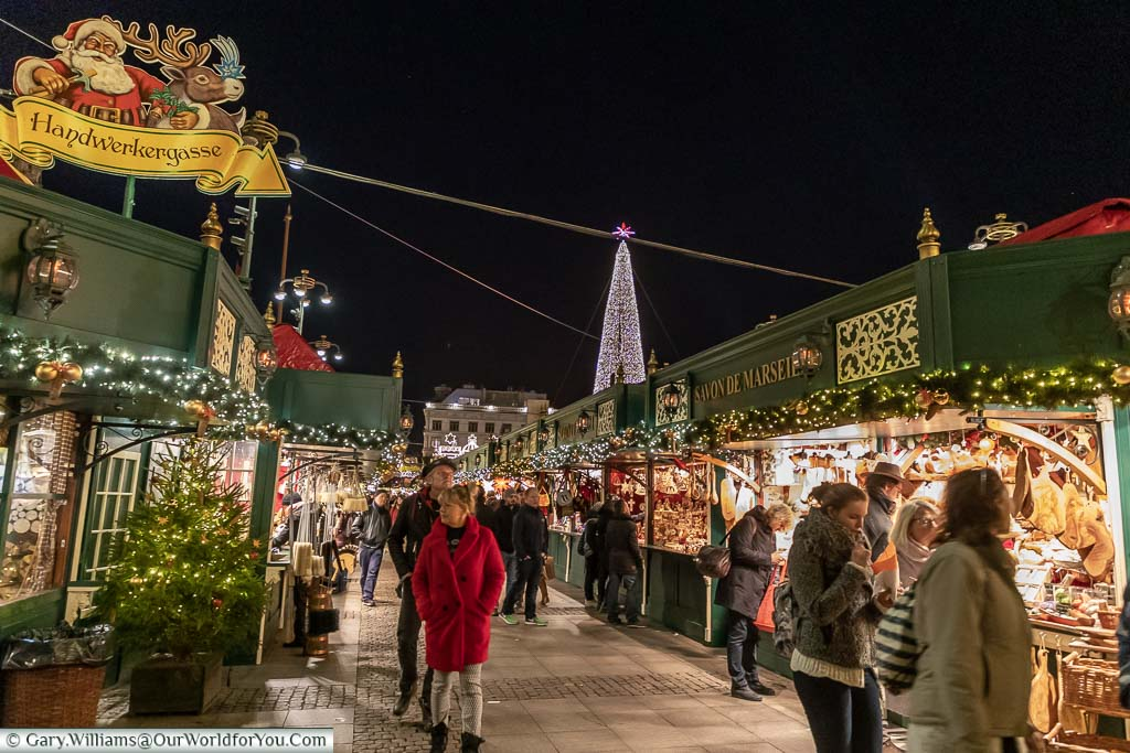People walking between rows of Christmas huts in the Weihnachtsmarkt in Hamburg late in the evening.